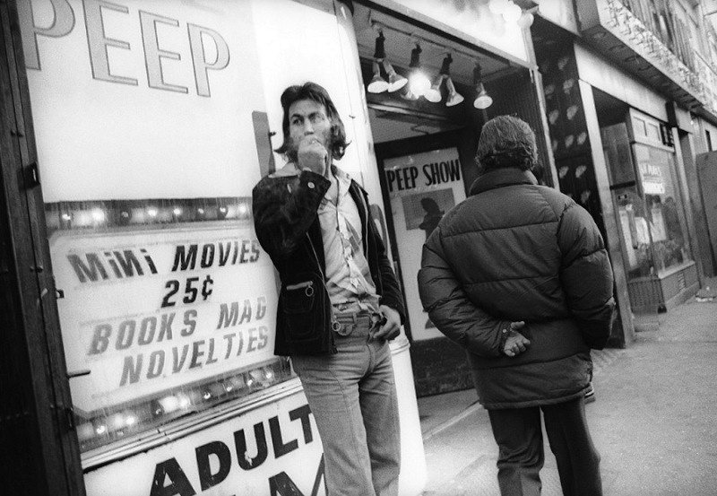 Man smoking outside adult theater, 1970s