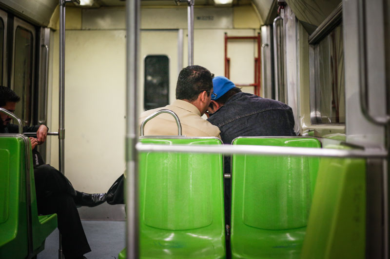 Two men leaning against each other on subway train