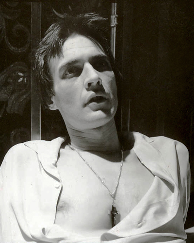 Tim Kent as the priest, looking distressed and wearing a cross necklace