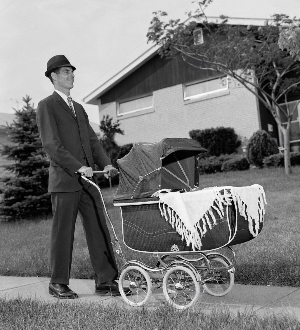 195s man in suit pushing baby carriage