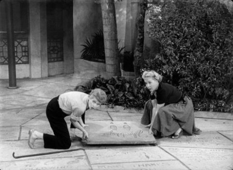 Lucy and Ethel attempting to steal John Wayne's footprints