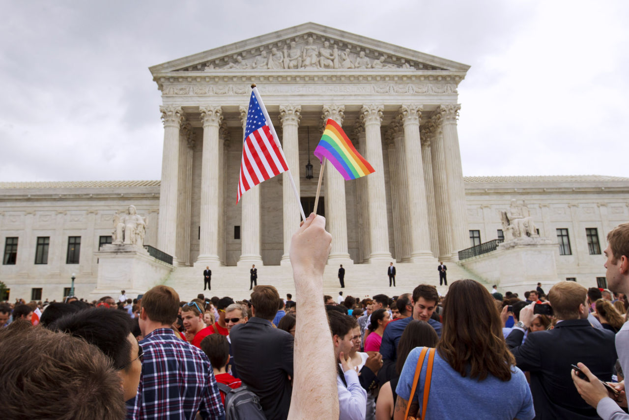 Person holding gay pride flag at protest in D.C.