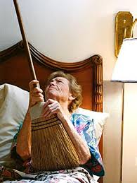 Old lady neighbor banging on ceiling with broom