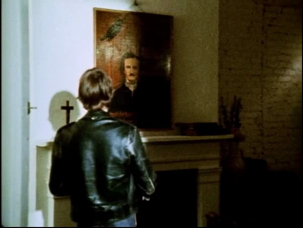 Man standing before a portrait of Poe and a cross