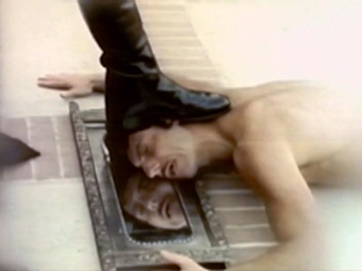 Still from Falconhead of boot stepping on a man with his face pressed into a mirror