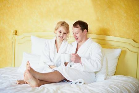 Straight couple in white bathrobes drinking coffee in bed
